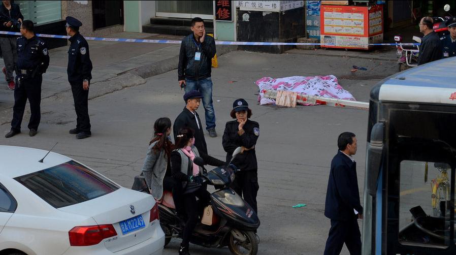 事故现场拉起长长的警戒线,民警正在勘查现场,坠楼男子尸体还停放在事