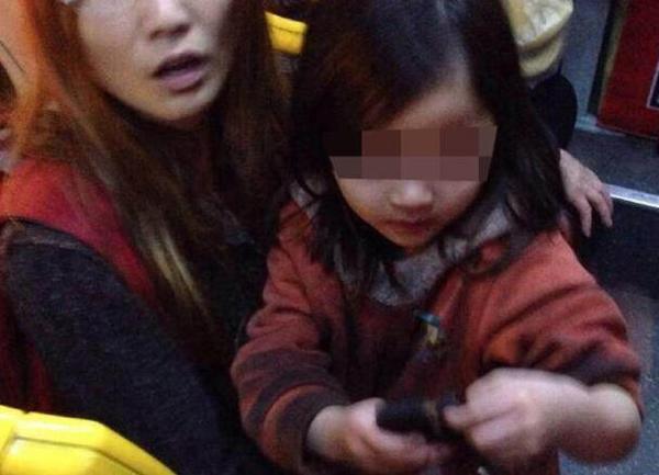 一个漂亮的小女孩光着脚手拿铁链乘公交