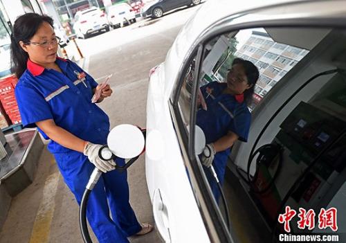 资料图:山西太原,加油站工作人员一边点钞一边加油。中新社发 武俊杰 摄