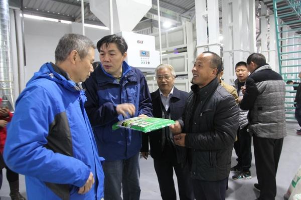 长阳土家族己治水县农业局局长程方(左二)即兴场了松父亲米包装情景