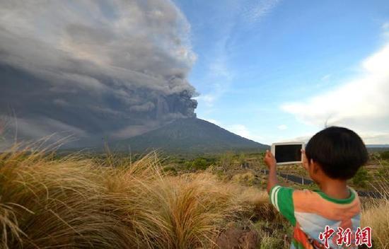 印度尼西亚巴厘岛上的阿贡火山25日下午再次喷发。中国驻登巴萨总领馆26日在官网上发布公告,紧急提醒中国公民近期谨慎前往巴厘岛旅游。 目前巴厘岛伍拉莱国际机场航空预警已升至最高级红色,一些国家的航空公司已取消往返巴厘岛的航班。  中新网消息,当地时间11月26日,印尼巴厘岛卡朗阿森,阿贡火山喷发。图为当地小朋友淡定拍照。 据报道,印尼国家减灾署发言人苏托波呼吁民众保持冷静,因为阿贡火山(Mount Agung)的警戒水平并没有提高。他说,该火山当天发生蒸汽喷发(phreatic eruption),喷