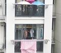 下雨了楼下被子还晒在外面:楼上住户在阳台撑3把伞