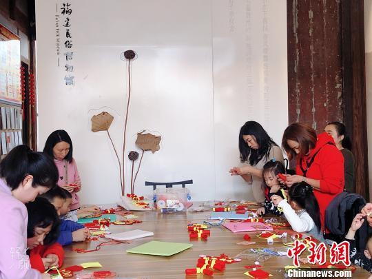 家长带着小朋友参与趣味手工体验活动。 叶秋云 摄